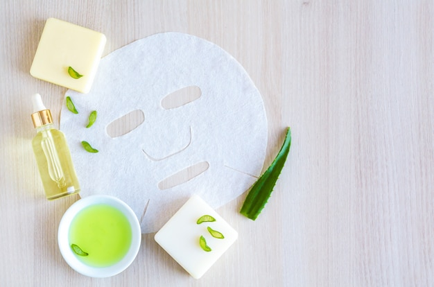 Natural cosmetics for facial skin care with aloe vera extract on a wooden with copy space. beauty concept. cosmetic tissue mask