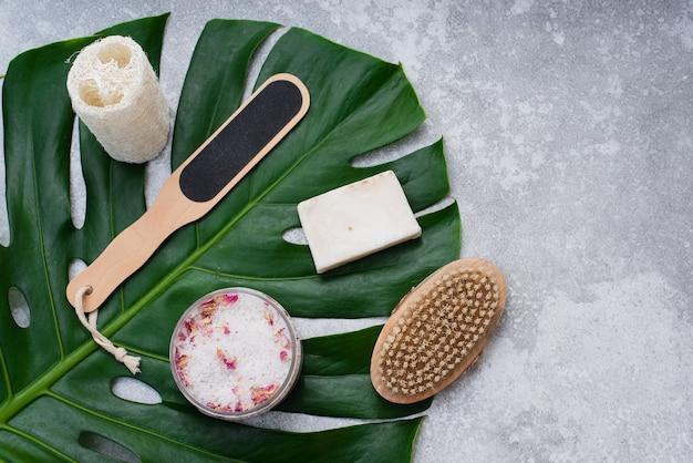 ヤシの葉を背景にした入浴用の天然化粧品。石鹸、バスソルト、ヘチマの手ぬぐい。