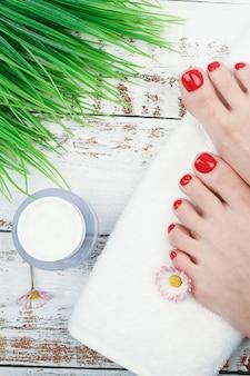 脚の自然化粧品。足の皮膚のための環境化粧品と自然化粧品のコンセプト。タオルの上に女性の足