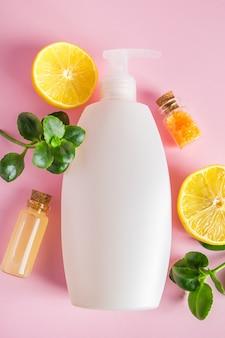 ピンクの背景に柑橘類を使用したレモンオーガニック美容製品を使用したスキンケア用の天然化粧品