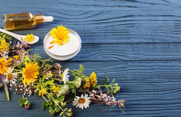 青いテーブルの上のハーブ成分からの自然化粧品