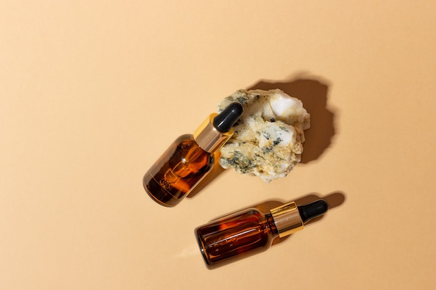 Natural cosmetics in glass bottles with a dropper stand next to a stone on a beige background with bright sunlight. the concept of natural cosmetics, natural essential oil