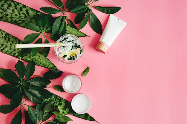 Natural cosmetics and green leaves on pink table.