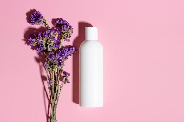Натуральная косметика в вид сверху белая бутылка на розовом фоне.