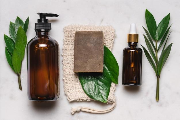 白い大理石の背景にガラス瓶に入った自然化粧品と植物の葉を持つ石鹸