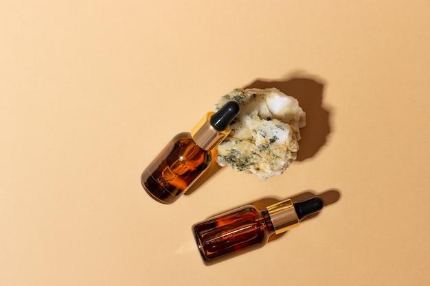 Натуральная косметика в стеклянных флаконах с капельницей стоит рядом с камнем на бежевом фоне при ярком солнечном свете. концепция натуральной косметики, натурального эфирного масла
