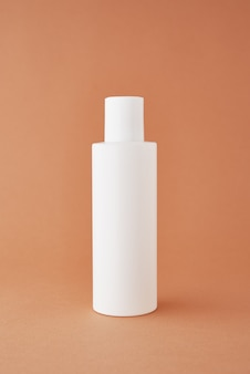 自然化粧品は、パステルカラーの背景に美容製品のコンセプトの白いボトルをモックアップします