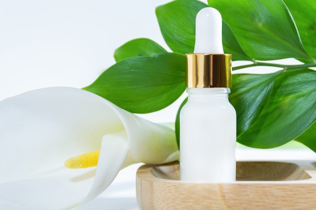Natural cosmetics, serum with dropper, calla lily flower and green leaves