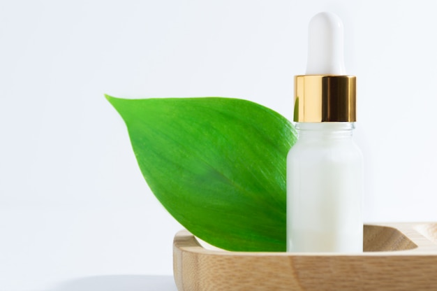 Natural cosmetics: serum with dropper and green leaves on white background.