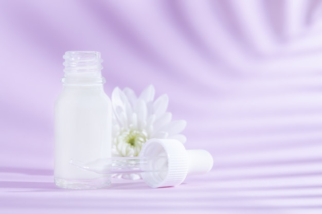 Natural cosmetics: serum with dropper and white flower on lilac background with shadow.
