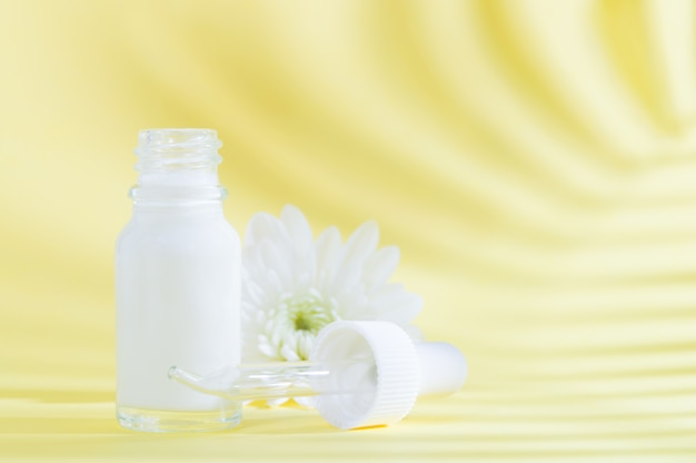 Natural cosmetics: serum with dropper and white flower on yellow background with shadow.