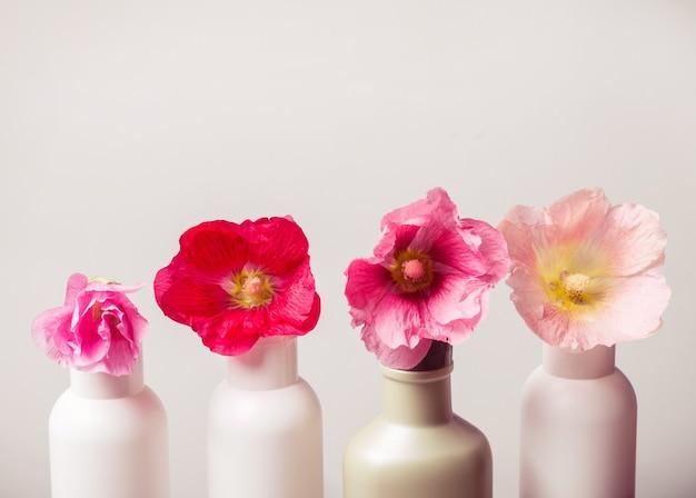 Набор натуральной косметики и цветы на сером фоне. концепция естественной экологии. тонированный
