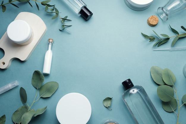 Натуральная косметика, средства по уходу за кожей, крем, лосьон, мыло на синем фоне с зелеными листьями