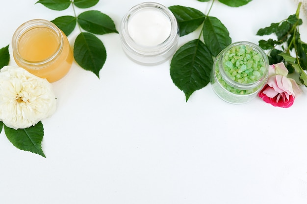Natural cosmetics on white background, copyspace. gel, mask and sea salt with green leaves, skincare products