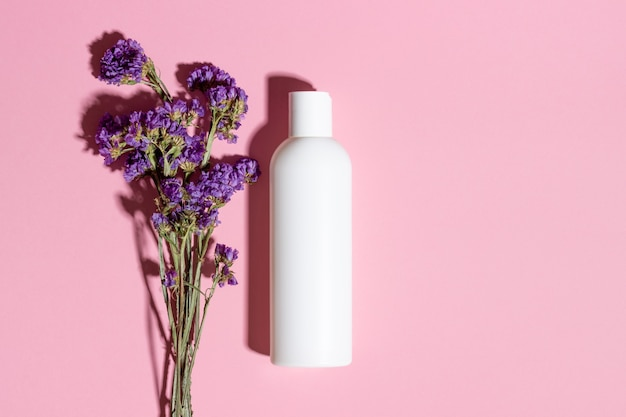 Natural cosmetics in a white bottle top view on a pink background.