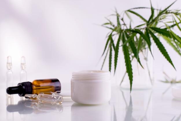 Натуральная косметика с маслом каннабиса. белая чистая банка с косметическим кремом и свежими зелеными листьями конопли.
