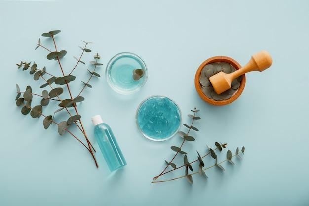 Натуральная косметика с травами эвкалипта в деревянной ступке. eucalyptus gel serum natural cosmetics in bottle с листьями и ветвями эвкалипта. эвкалиптовое масло в косметической медицине по уходу за кожей.