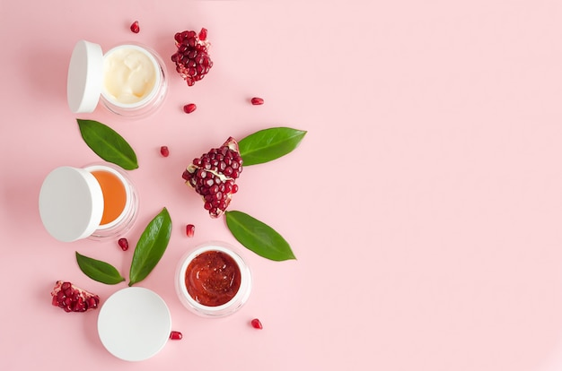 Natural cosmetics with fruit aha acids, pomegranate extract on pink background. beauty concept. jar with cream, mask, scrub, peeling for professional facial skin care. banner, layout, copy space