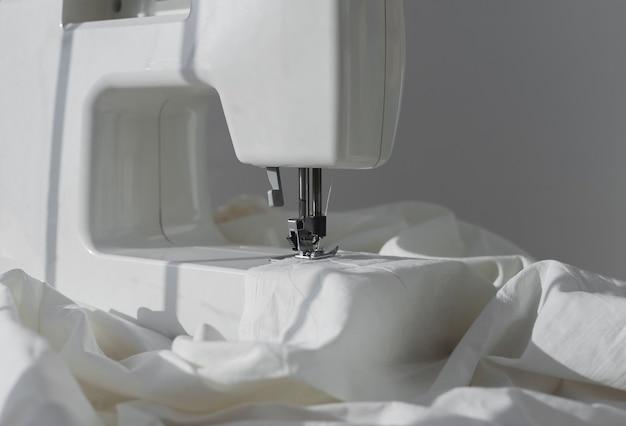 Ткань из натурального хлопка на швейной машине крупным планом концепция малого бизнеса