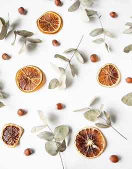 Natural creative composition of dry branches of eucalyptus and orange dry slices and hazelnuts nuts