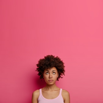 Natural curly african american woman looks thoughtfully above, has some thought in mind, wears casual clothes, stands against pink wall, copy space for your promotion, recalls something