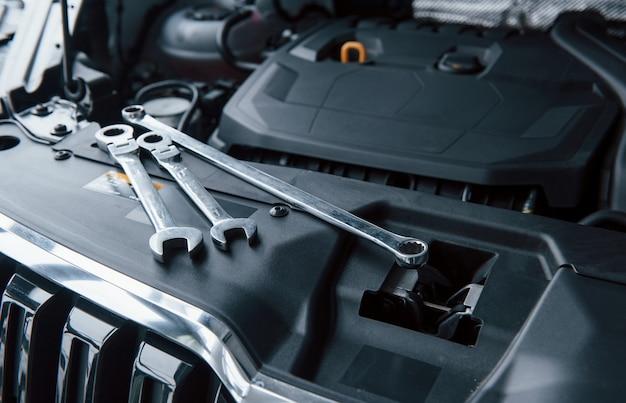 Естественный дневной свет. инструменты для ремонта, лежа на двигателе автомобиля под капотом