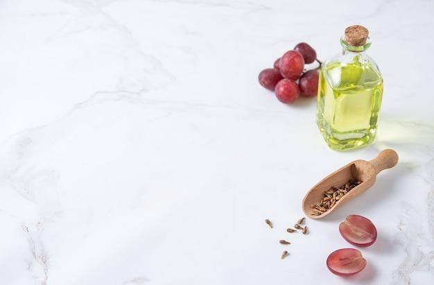 흰색 대리석 배경에 유리병에 든 천연 식이 및 채식주의 포도씨 오일. 건강한 음식과 생활 방식. 상위 뷰 및 복사 공간
