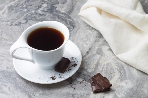 Натуральный напиток цикорий в белой чашке и блюдце на мраморном столе с кусочками шоколада.