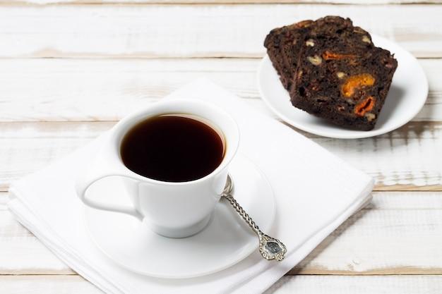 Натуральный напиток цикорий в белой чашке с блюдцем с фруктами и ореховым хлебом, на деревянном столе.