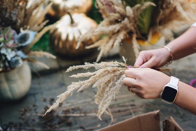 素朴な感謝祭の構成のための自然な乾いた草。フロリスティックアート秋の装飾。秋の休日のための家の装飾。