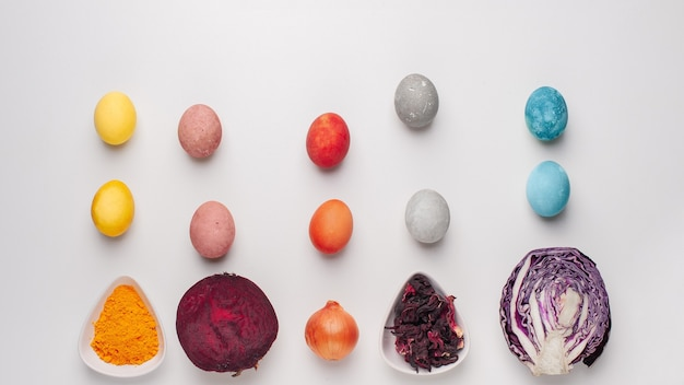 Natural dye for easter eggs - red cabbage, beetroot, carcade, turmeric and onion skin on light background