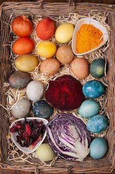 イースターエッグ用の天然染料-バスケットに入った赤キャベツ、ビートルート、カーケード、ターメリック、タマネギの皮