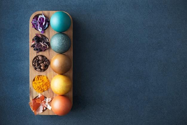 イースターエッグ用の天然染料-赤キャベツ、カーケード、コーヒー、ターメリック、タマネギの皮。材料と自家製の着色されたイースターエッグ。