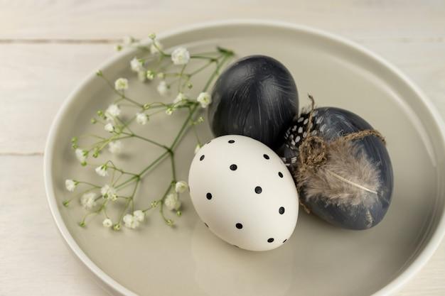 소박한 나무 배경에 접시에 자연 염색 된 회색 부활절 달걀. 높은 각도의 관점.