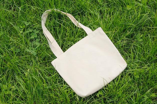 Natural eco bag, mockup on a wall of green grass, top view.