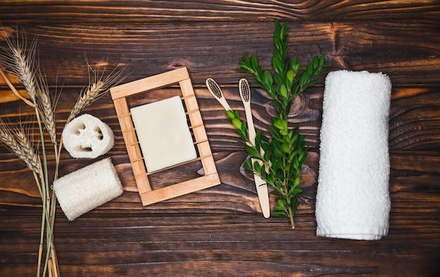 Натуральные эко бамбуковые зубные щетки, люфа, кокосовое мыло, моющее средство ручной работы и люфа на деревянном фоне