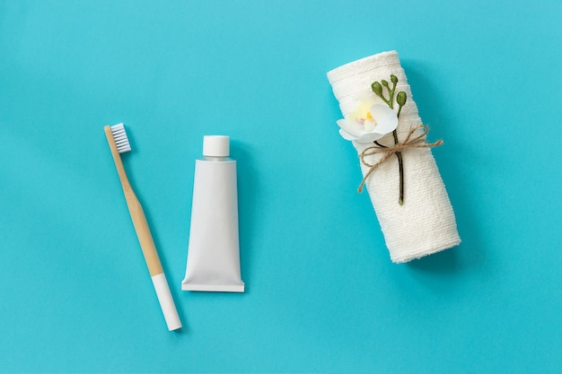 Natural eco-friendly bamboo brush, white towel and tube of toothpaste. set for washing