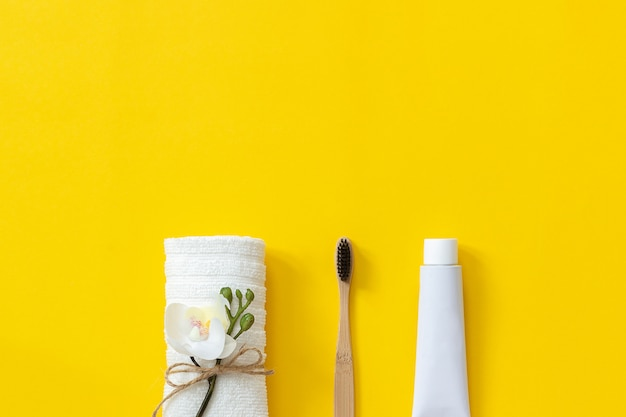 Natural eco-friendly bamboo brush, white towel and tube of toothpaste