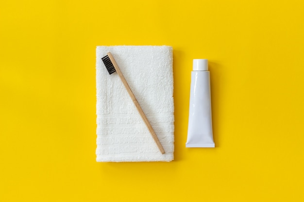 Natural eco-friendly bamboo brush on white towel and tube of toothpaste.