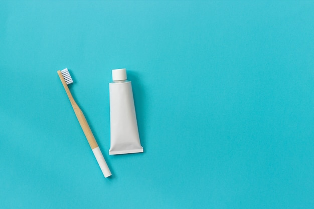 Natural eco-friendly bamboo brush with white bristles and tube of toothpaste. set for washing