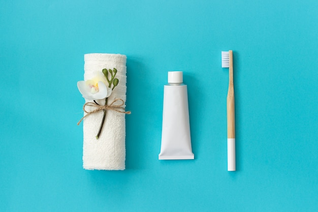 Natural eco-friendly bamboo brush with white bristles, white towel and tube of toothpaste. set for washing