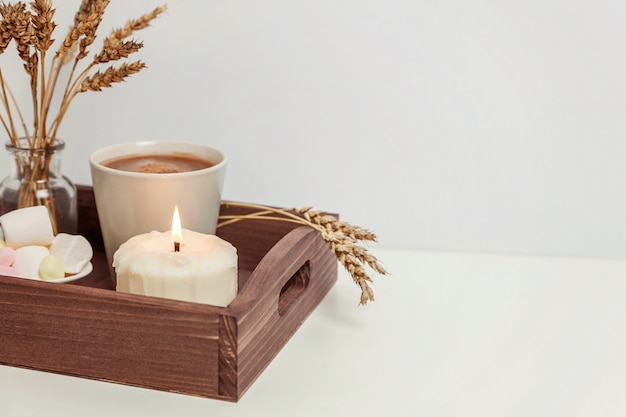Natural eco home decor with cup coffee marshmallow and candle on wooden tray