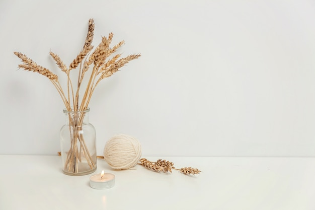 Natural eco home decor with wild rye bouquet in glass vase near white wall
