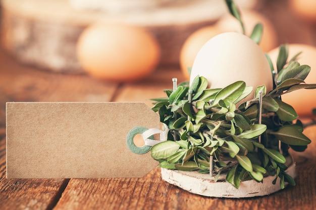 束の植物からのバスケットの自然な卵と晴れた朝の木製のテーブルのテキストの空のタグ。環境にやさしいイースターコンセプト。