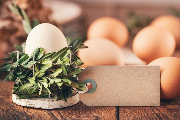 무리 식물에서 바구니에 자연 계란과 나무 테이블에 텍스트에 대 한 빈 태그