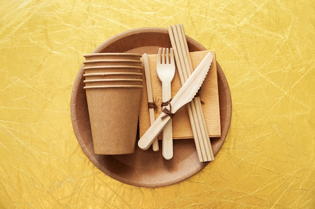 Natural environmentally friendly bamboo and paper tableware. the concept of recycling, nature conservation and saving the earth. golden surface.
