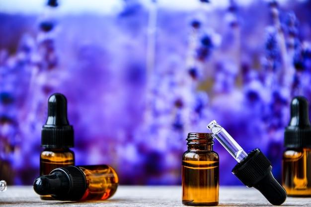 Натуральное эфирное масло капает из пипетки в бутылку против цветов лаванды, крупным планом. бутылки с натуральным эфирным маслом лаванды на деревянном столе на размытом фоне