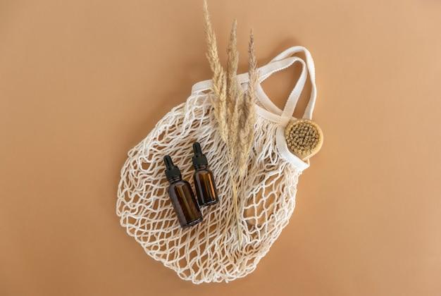 天然エッセンシャルオイルまたは美容液スポイトボトル、天然フェイシャルブラシがメッシュバッグの上にあります