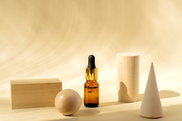 Natural essential oil or serum in a brown glass bottle with wooden podiums