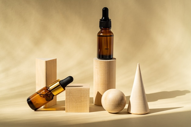 Natural essential oil or serum in brown glass bottles on a wooden podiums
